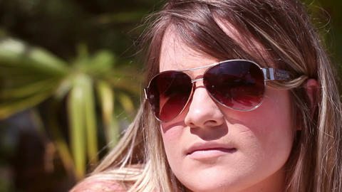 Camera pans to cute attractive blonde millennial woman in sunglasses on tropical Footage