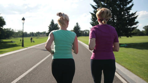 Back view of senior fitness women running on road Footage