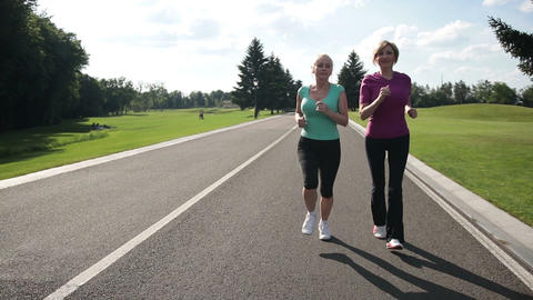 Cheerful adult fit women jogging in the park Live Action