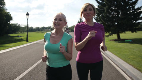 Adult female joggers pursuing activity outdoors Live Action