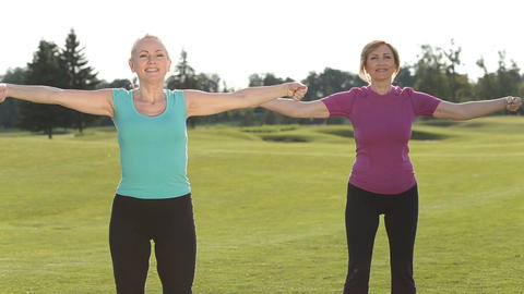 Sporty fitness ladies warm up in park Live Action