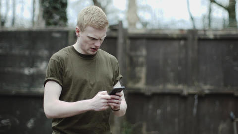 Army soldier checking mobile phone Bild