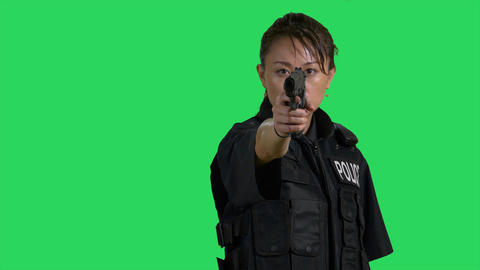 Asian Chinese policewoman pointing pistol with one hand on green screen Live影片