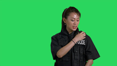 Asian Chinese policewoman talking on police radio on green screen Live影片