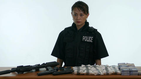 Asian female police officer by table of seized goods 1 Live影片