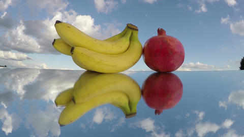 Three bananas and pomegranate on mirror, time lapse 4K Footage