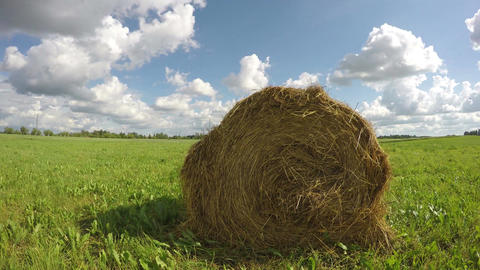Haystack in field on cloudy day, time lapse 4K Footage