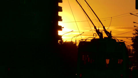 1080p Passenger Trolleybus Crosses Frame Against Sunset in Evening City Footage