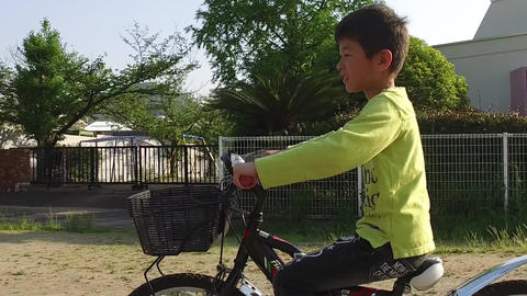 A boy riding a bicycle in the square ビデオ