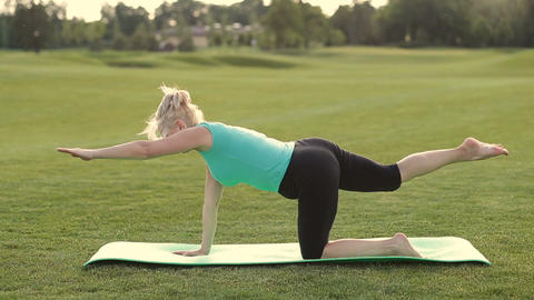 Attractive adult woman practicing yoga in park Footage