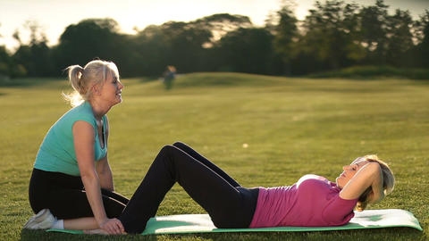 Lady doing abdominal crunches exercise on mat Live Action