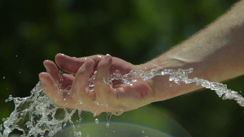 Stream of water Male hand runs through water fast shutter speed. Slow motion Image
