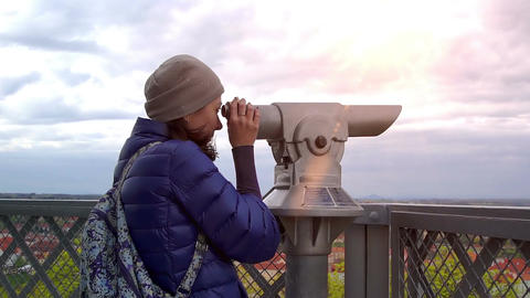 Young caucasian woman adjusts the focus and looks to the telescope Footage