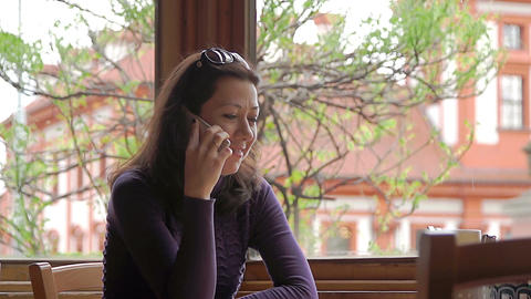 Beautiful woman talking on cellphone in cafe Stock Video Footage