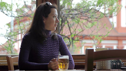 Pensive woman drinking beer while sitting in cafe Live Action