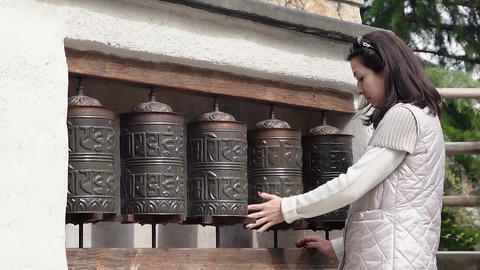 European woman spins prayer wheels Footage