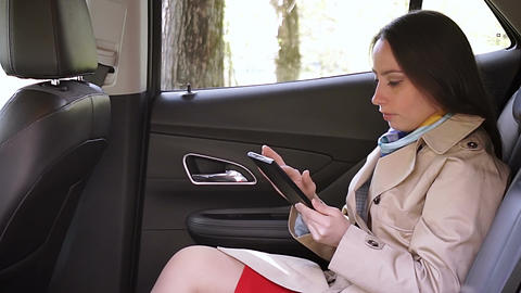 Young woman using tablet in the car Live Action