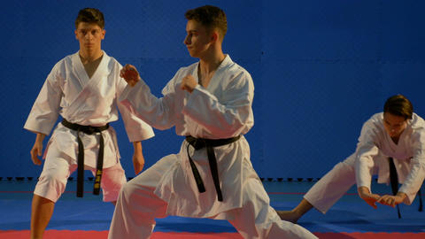 Three teenagers doing warm up before martial arts competition Footage