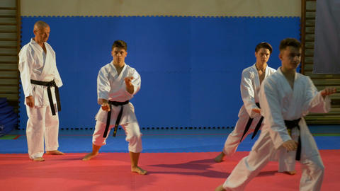Teenagers martial arts practitioners performing kata at the dojo with sensei kar Footage