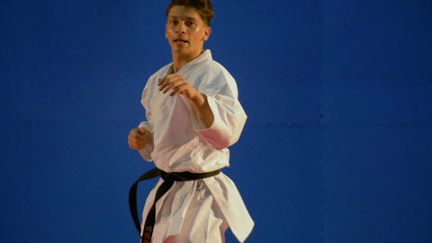 Handsome young black belt karate man exercises punching in slow motion Footage