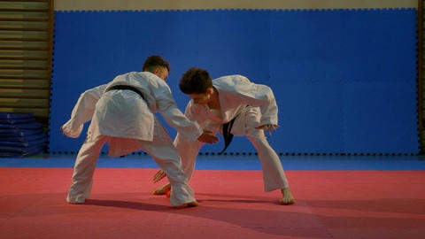 Two boys dressed in white karate kimonos playing with a glove at the dojo Footage