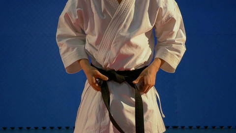 Close up of man tying up knot of black belt on special karate kimono equipment i Footage