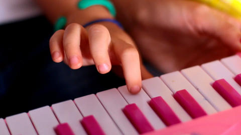 Macro Little Finger Presses Keys on Pink Piano One by One Footage