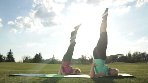 Sporty ladies doing upside down seal pose outdoors Live Action