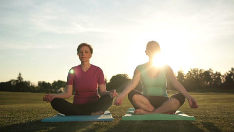 Serene women meditating in half lotus at sunset Footage
