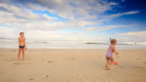 Kids Girl with Pigtail Boy Throw Catch Ball on Sand Beach Footage