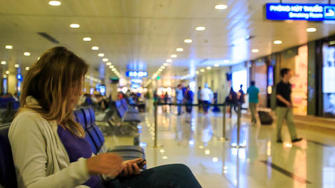 Blond Girl Sits down on Waiting Bench in Airport Terminal Footage