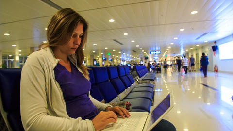 Closeup Blond Girl Sits on Chair Works on Laptop in Terminal Footage