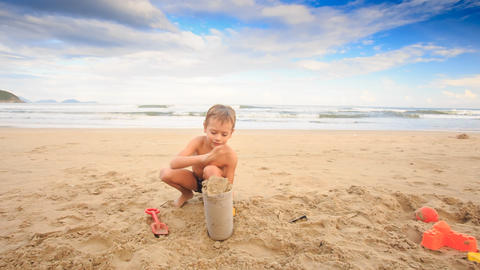 Small Boy Plays with Wet Sand Fills Bucket on Sea Beach Footage