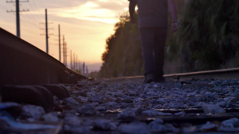 Lone man walks down railroad tracks into sunset, 4K Footage