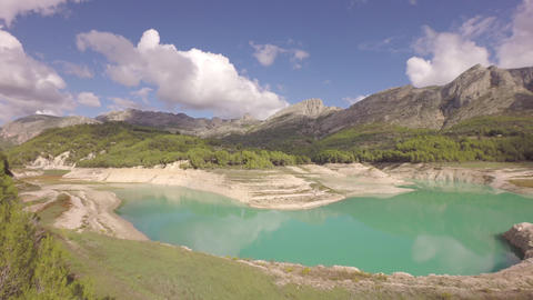 Aerial flying backwards over reservoir and dam at Guadalest and mountains in bac Footage