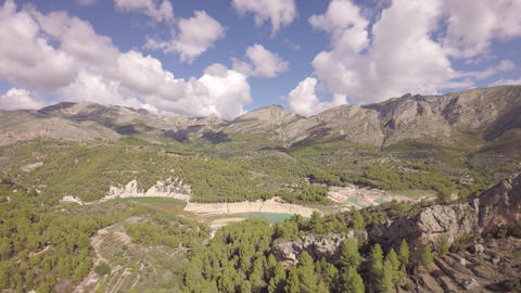 Aerial flying backwards of reservoir and dam at Guadalest and mountains in backg Footage