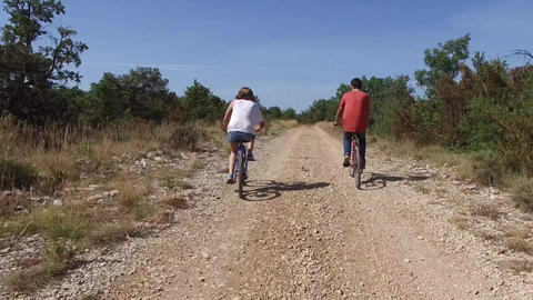 Two cyclists riding on a rural track in the garrigue or scrubland in the South o Footage