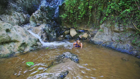 Small Girl Starts to Swim in Stream Water by Waterfall Footage