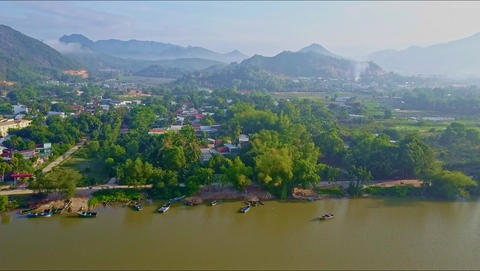 Drone Flies up from Green Quiet River over Town on Bank Footage