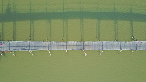 Drone Approaches to Bridge Reflected in River with Scooters Footage