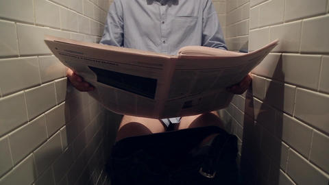 A man reads a newspaper in the toilet Footage