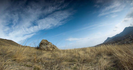 The clouds fly over a stone on a hill above the valley. Time-lapse. Feeling of t Live Action