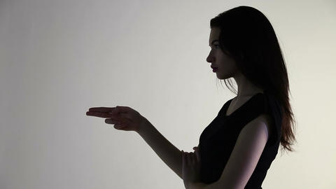 Young woman in evening dress gestures with a gun Live Action