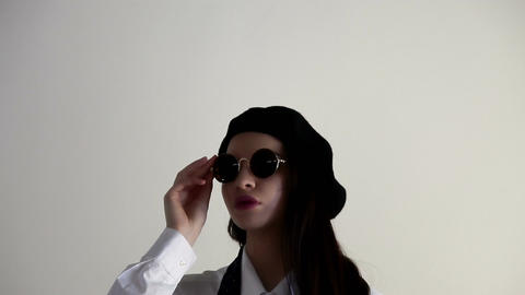 A Young woman in shirt, sunglasses and beret, on the white background Live Action