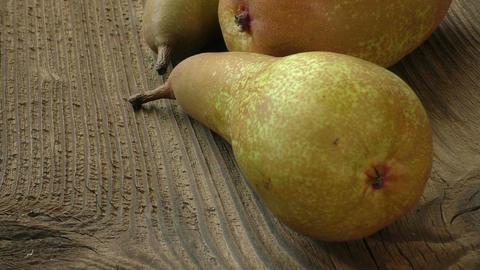 Three ripe juicy pears on a dark wooden table Footage