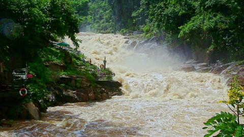 Stormy Mountain River Cascade Flows among Green Rocky Banks Footage
