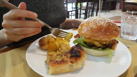 Young Woman Eating Potatoes and Hamburger in Restaurant Filmmaterial