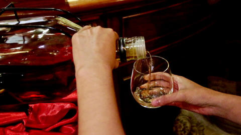 Closeup Girl Pours Alcohol into Wine Glass Bend Bottle in Bar Footage