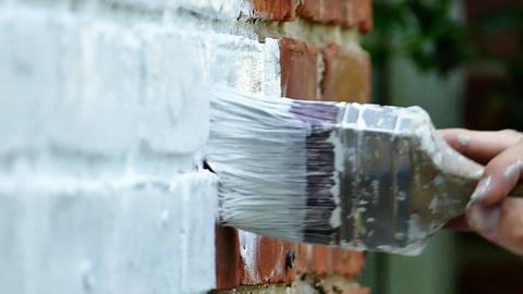 Painting brick house with brush slow motion