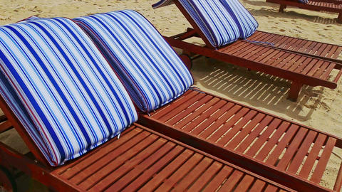 Closeup Brown Chaise-longues with Striped Mattresses on Beach Footage